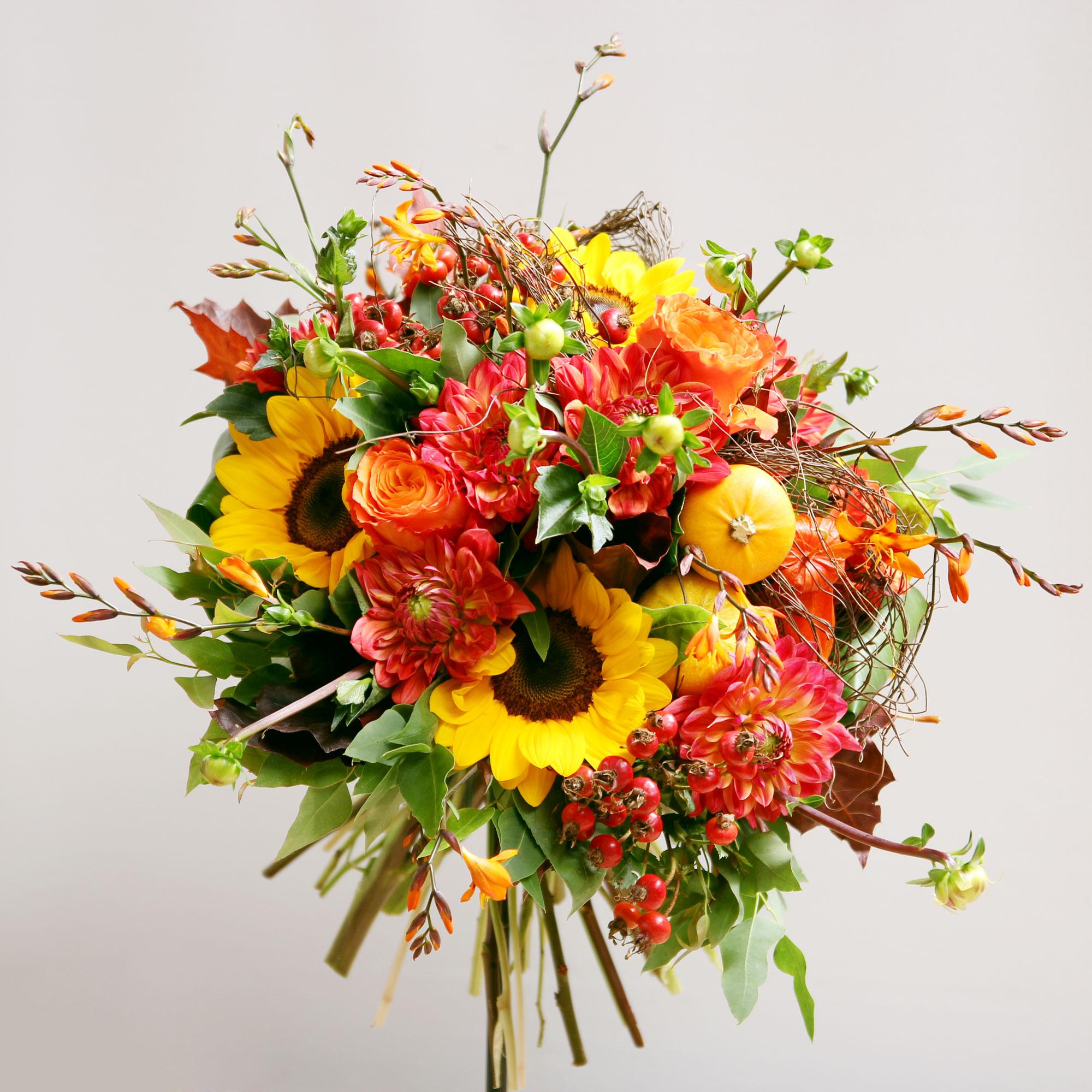 Bouquet de fleurs composé de tournesols, dahlias, crocosmias, baies de rose, roses.