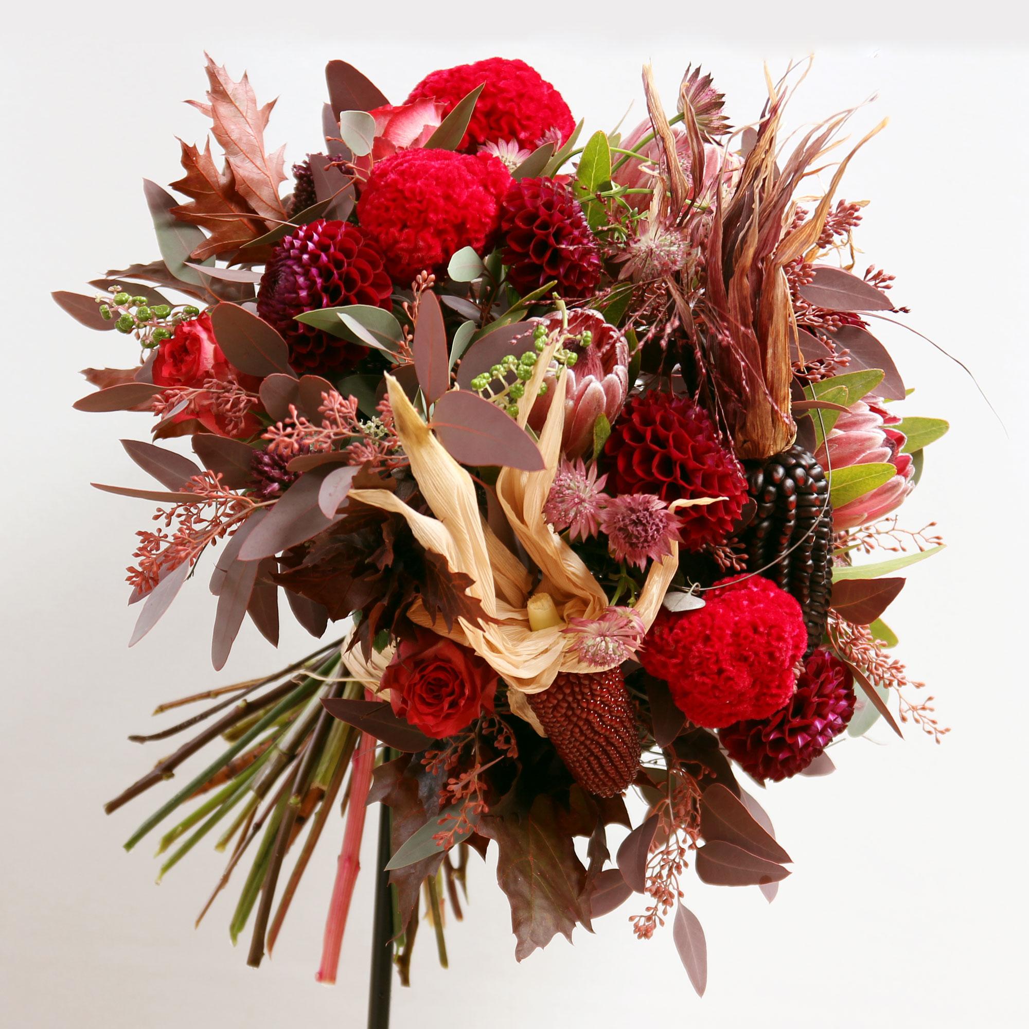 Bouquet composé de dalhias, de célosies crête de coq, de banksias, d'astrancias, d'eucalyptus, de roses et d'épis de maïs.
