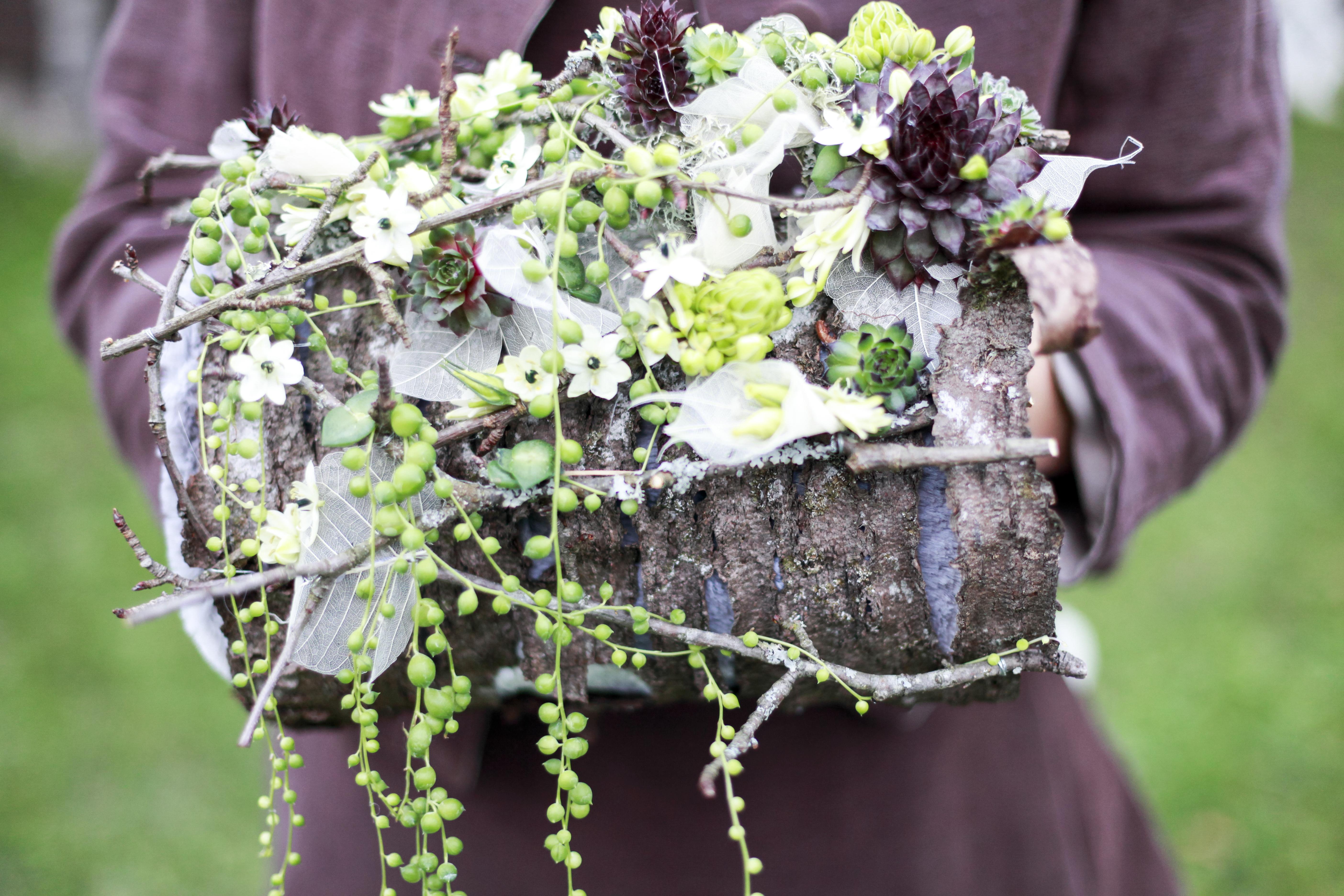 Le bouquet manchon est réalisé à partir d'écorce de bois, de petites plantes grasses et de fleurons d'ornithogalum arabica.
