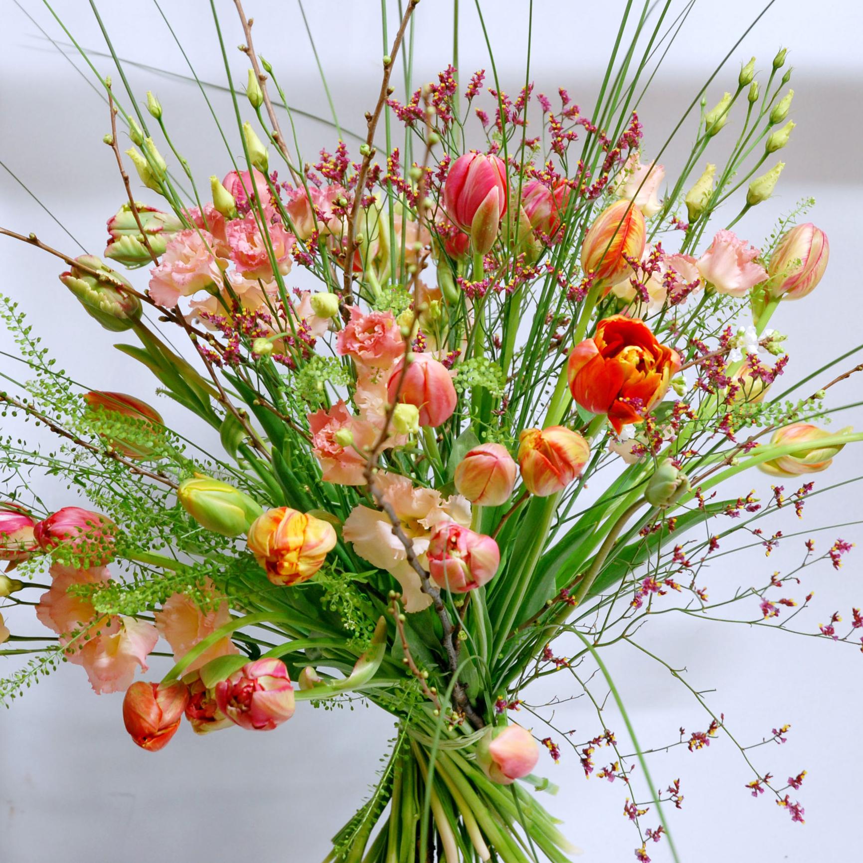 Bouquet de fleurs compose de tulipes, de lisianthus, de thalspis, de limoniums, de stealgrass et de branchages.