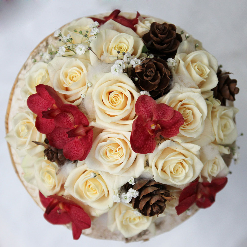Le bouquet sur structure en écorce avec roses crème, orchidées vanda bordeaux et pommes de pins.